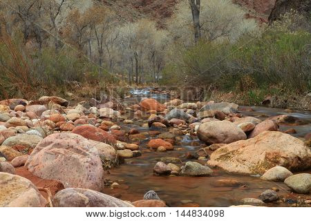Boulder and rock strewn creek in wooded valley