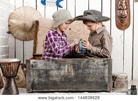 little boy and girl study globe sitting in big old chest