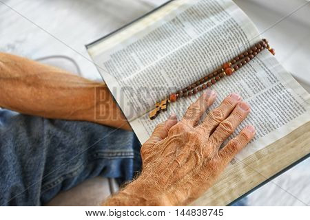 Old man holding and reading Bible