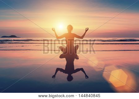 Female silhouette sitting in yoga pose on the beach by sea at sunset.