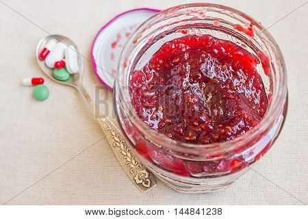 Different tablets on a spoon. Raspberry jam. Concept - the disease treatment prevention.