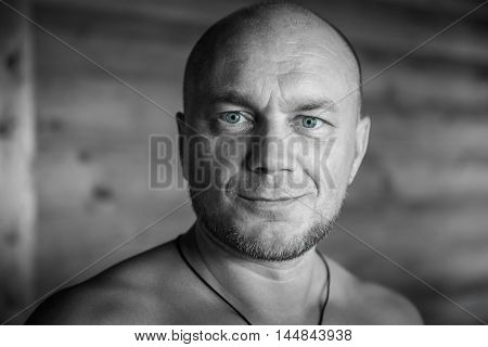 Black and white portrait of a smiling bald man