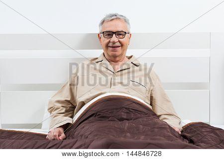 Happy senior man is lying in bed.