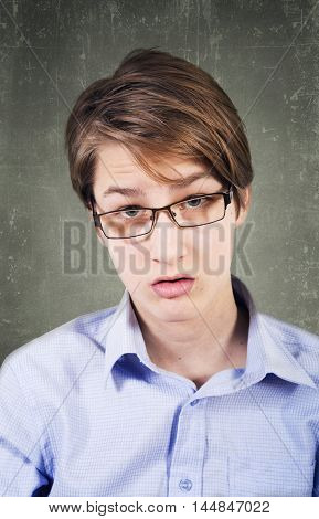 Teen in glasses and braces against the background of a board at school