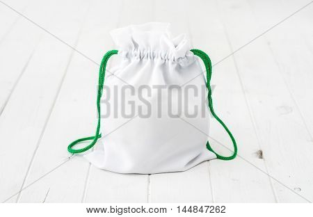 full white fabric gift bag with green ties on wooden table