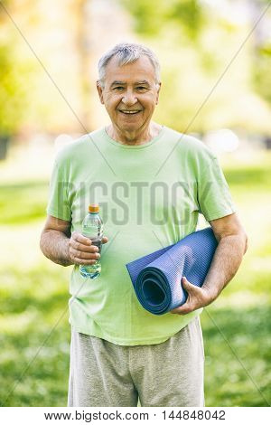 Senior man is ready for exercise in park. Active retirement. Image is intentionally toned.