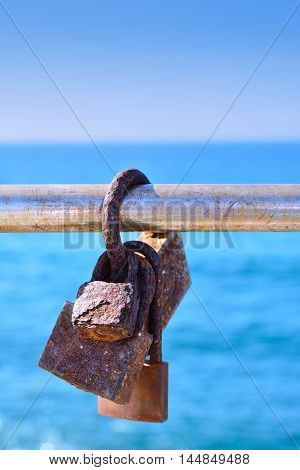 Close-up of rusty love locks hanging on metal railing in sunlight