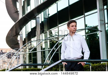 serious teenager in a suit near the business center