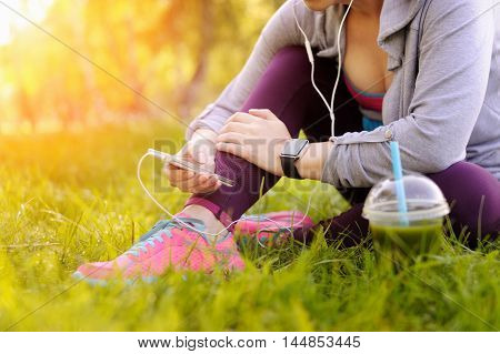 Sporty Woman Sitting On Grass In Park.
