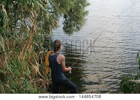 Fisherman holds a fishing rod on lake among bushes. Fisherman with impatience waits fish get bait.