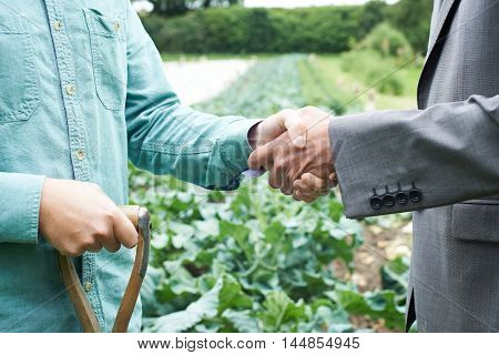 Close Up Of Farmer And Businessman Shaking Hands