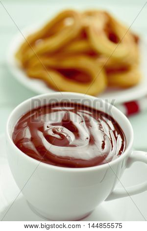churros con chocolate, a typical Spanish sweet snack, on a rustic pale blue wooden table