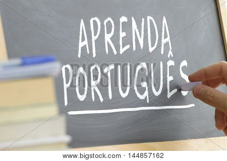 Hand writing on a blackboard in a Portuguese class. Some books and school materials.