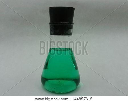 Flat-bottomed glass flask with green chemical solution