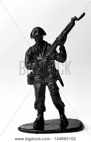 Dramatic toy army soldier carrying rifle to battle in black and white image