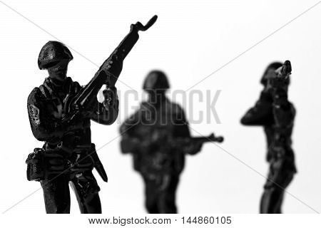 Dramatic toy army soldiers lined up for battle in black and white image