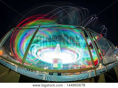 Amusement park ride long exposure night light blurs