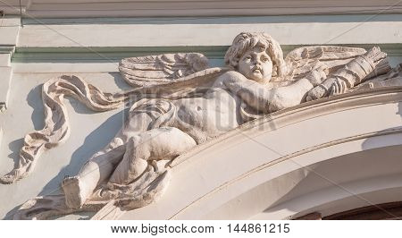 Cupid sculpture adorns the gable of an old building