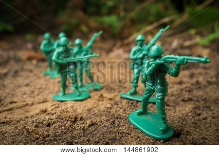 Green toy soldiers march forward ready for battle