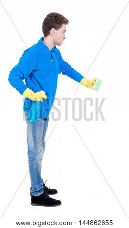 side view of a cleaner man in gloves with sponge and detergent. girl watching. Curly boy in a warm blue sweater sponge.