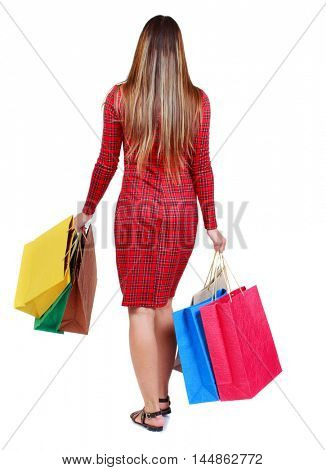 back view of going woman with shopping bags . girl in red plaid dress is waving colored bags in their hands.