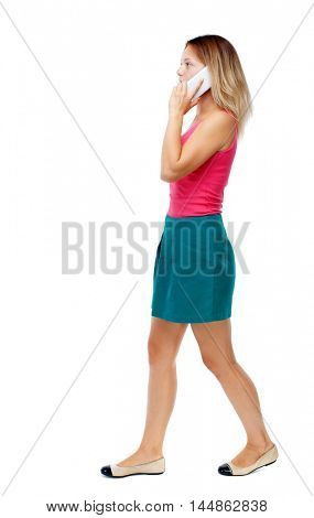 side view of a woman walking with a mobile phone. beautiful girl in motion. Isolated over white background. Blonde in a red sweater and green skirt talking on the phone while walking.