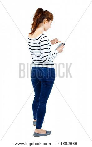 back view of standing young beautiful woman using a mobile phone or tablet computer. Girl in a striped sweater standing sideways and running on the tablet.