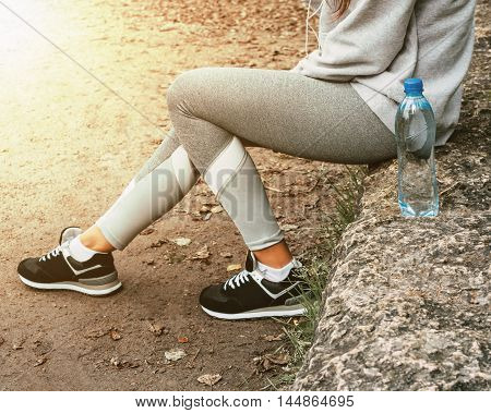 Woman sitting in the park with a bottle of water and resting after a training