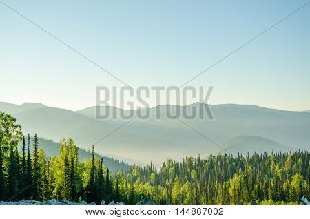 thick morning fog in the summer forest. wavy colorful mountains. motley mountains. morning light falls on the colorful mountains