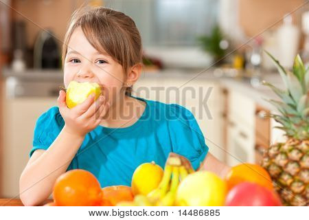 Healthy eating - child eating an apple, lots of fresh fruit on the table in front
