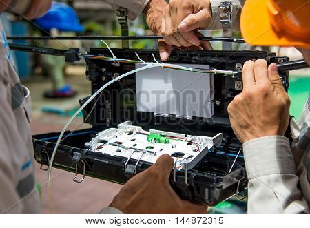 Technicians are install cabinet on fiber optic cable.Blur images with back lighting.