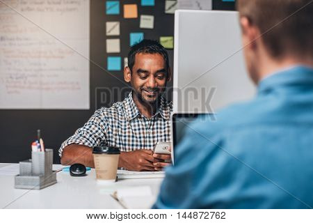 Smiling designer sitting at his desk checking his cellphone and working on a computer while sitting in front of a colleague in an office
