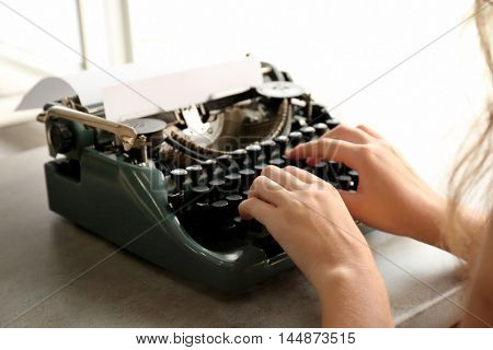 Woman typing on the typewriter at the table