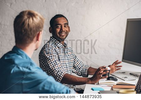 Two smiling designers collaborating on a project together in front of a computer while working in an office