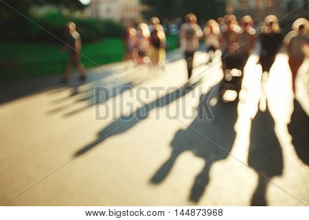 Blurred people background in magic sunset light with lond shadows.