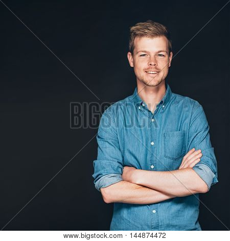 Studio portrait of a smiling and confident young entrepreneur standing with his arms crossed in front of a dark background