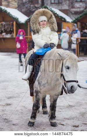 little girl in a white jacket riding a pony