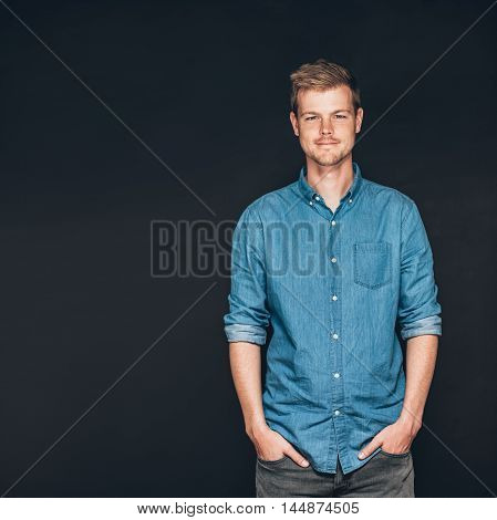 Studio portrait of a smiling and confident young entrepreneur standing with his hands in his pockets in front of a dark background