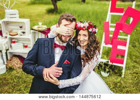 Wedding couple embracing each other against the ladder with word love. Moment of joy