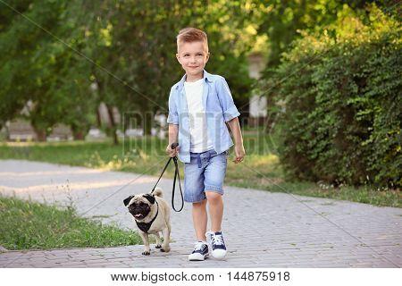 Cute boy with pug dog in park