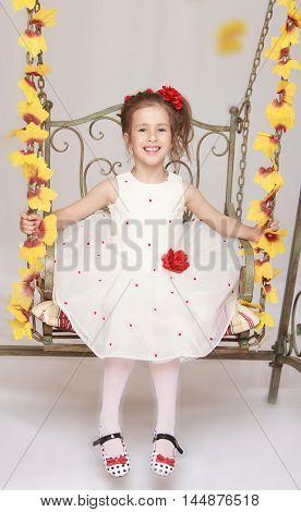 Cute little girl in white dress swinging on a swing