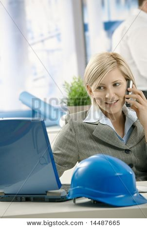 Smiling architect talking on phone looking at computer screen in office.?