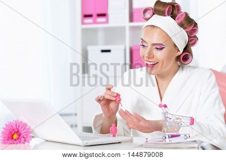 portrait of Beautiful woman in hair curlers with laptop and  shopping cart