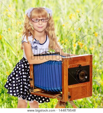 Adorable little blond girl wearing glasses and fancy polka-dot dress, next to a vintage camera.On the background of green grass and yellow wild flowers, blurring the background.