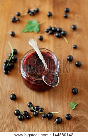 Blackcurrant jam in jar on wooden background. Top view.