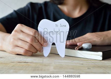 dentist appointment paper cuts tooth shape write the word that dentist and date in woman hand