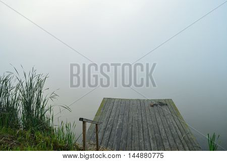fog over the water in the morning with place for fishing, pier. mist over the lake in the early morning
