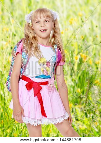Happy little girl in a pink short skirt with a knapsack on his shoulders. Close-up.On the background of green grass and yellow wild flowers, blurring the background.
