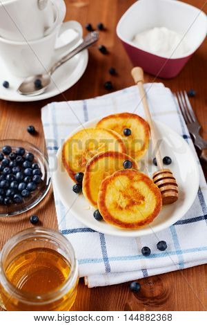 Fritters of cottage cheese with honey, sour cream and bilberry or blueberry on a white plate. Delicious breakfast.