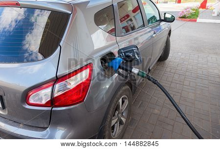 TVER REGION, RUSSIA - JUNE 26 2016: Pumping gasoline fuel in passenger car at gas station